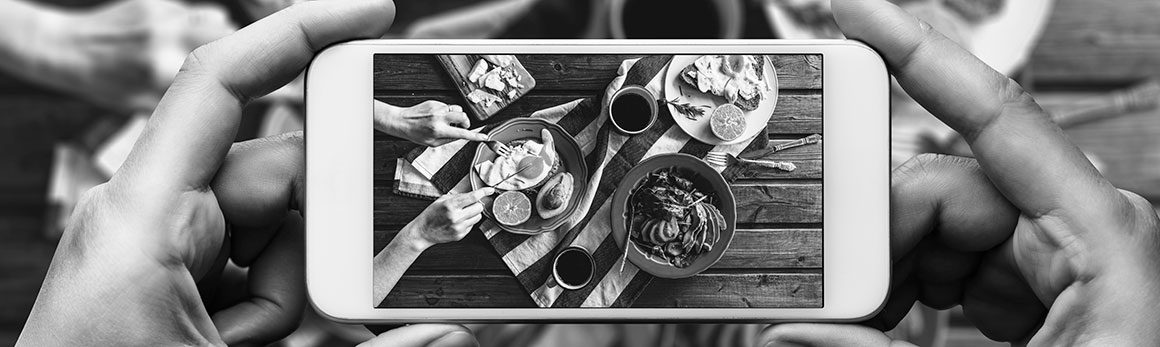 Point-of-view of two hands holding an iphone to take an overhead shot of a delicious spread of eggs, cheese and other foods.