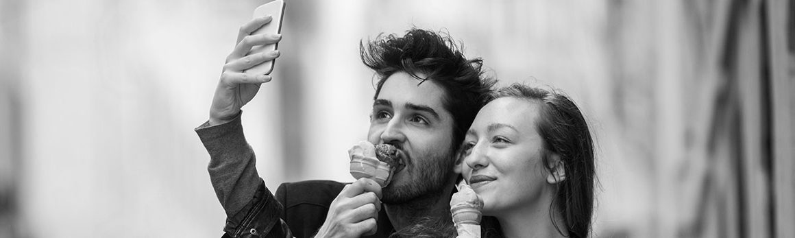 A gen-z woman and gen-z man eat ice cream cones while taking a selfie.
