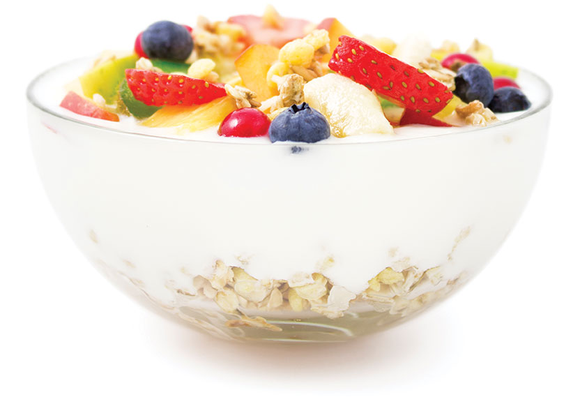 A glass bowl with grains, yogurt and various fruits and granola.