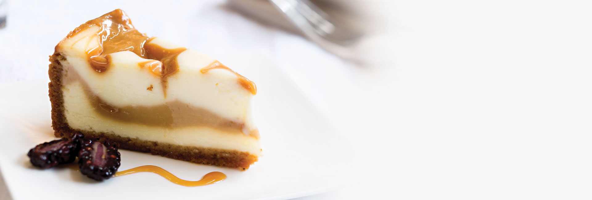 A slice of caramel cheesecake on a brown crust served on a white plate with a sliced blackberry and topped with caramel drizzle.